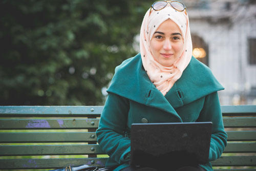 photo of woman in coat with laptop